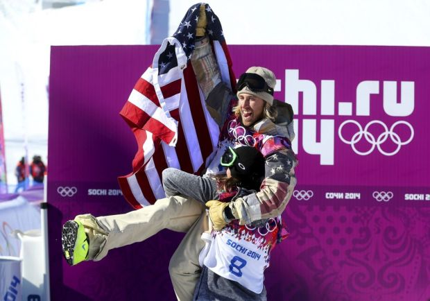 Sage Kotsenburg of the U.S. is lifted in the air by Staale Sandbech of Norway after Kostenburg won the men's snowboard slopestyle final in Krasnaya Polyana, Russia.